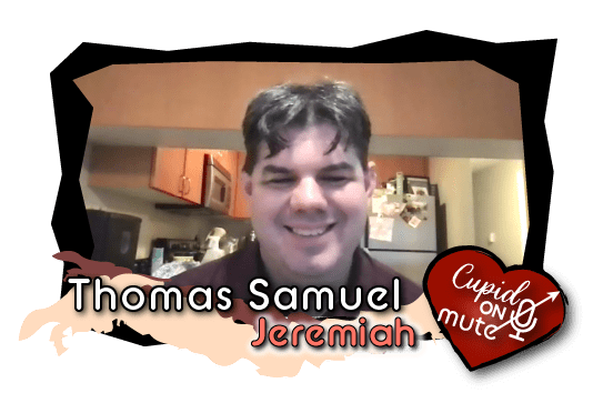 Thomas, with center parted dark hair and a button down, smiles earnestly into the camera.